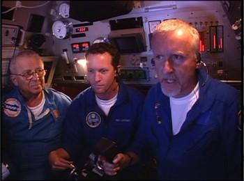 Posádka ponorky, vpravo Cameron ovládáající sondu